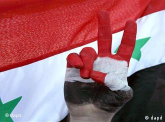 A Syrian protester flashes a V-victory sign with his hand painted in Syrian national colors