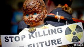 Doll with burnt head and sign reading Stop killing the future