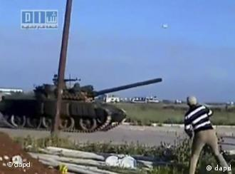 This video image taken from amateur video released by Sham News Network, a Syrian Freedom group, shows a man throwing an object at a tank in Daraa, Syria