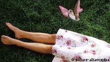 Die Beine und Schuhe einer jungen Frau in einem Kleid liegen im grünen Gras. Undatierte Aufnahme. Model released.