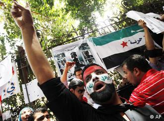 Syrian protesters chant angry slogans as they protest against the ongoing violence in Syria in front of the Syrian embassy in Cairo, Egypt, Tuesday, April 26, 2011.