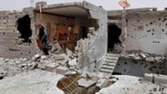 Neighbours examine the damage to a house which was struck by a shell in Misrata, Libya, Monday, April 25, 2011. Gadhafi's troops on the outskirts of Misrata unleashed more shells into the city Monday, hitting a residential area and killing 10 people, including five members of one family, according to a doctor in Misrata. (AP Photo)