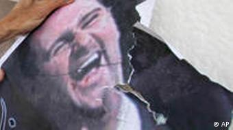 A Syrian protester beats a poster of Syrian President Bashar Assad with a shoe, as he attends protest against the on going violence in Syria, in front of the Syrian embassy in Cairo, Egypt, Tuesday, April 26, 2011.Gunfire reverberated Tuesday in the southern Syrian city of Daraa where the dead still lay unclaimed in the streets a day after a brutal government crackdown on the popular revolt against President Bashar Assad, residents said. (AP Photo/Khalil Hamra)