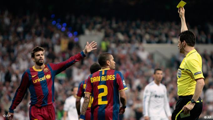 Barcelona's Daniel Alves from Brazil, center, reacts as the referee shows him a yellow card