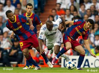 Real Madrid's Lassana Diarra, center, battles with Barcelona's Seydou Keita