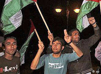 Palestinians wave flags and chant slogans in support of a reconciliation between the rival Fatah and Hamas movements