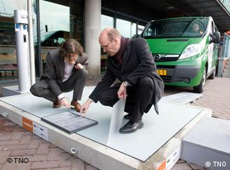 Two men show how the solar panel works