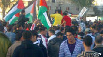 Busy Palestinian street with people waving flags