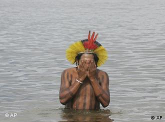 Indígena lava o rosto no Rio Xingu durante protesto contra hidrelétrica
