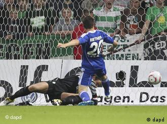 Wolfsburg's Sascha Riether scores as Bremen's keeper lunges for the ball