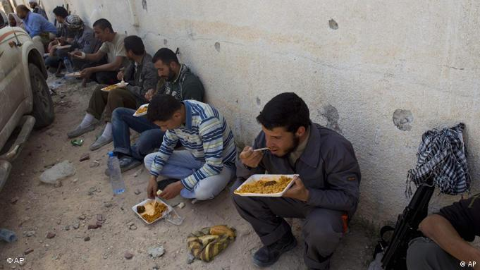 Rebel fighters pause for lunch in the besieged city of Misrata, Libya, Friday, April 29, 2011. (Foto:Bernat Armangue/AP/dapd)