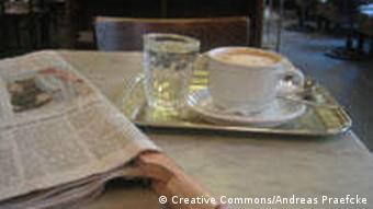 Ein Serviertablett, ein Glas Wasser und eine große Tasse mit Kaffee, ein Häferl