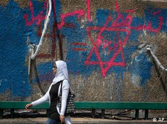 An Egyptian woman walks past an anti Israel graffiti with Arabic that reads Down with Israel near the Israeli embassy in Cairo, Egypt Monday, May 16, 2011. Egyptian riot police fired tear gas and live ammunition overnight to disperse thousands of pro-Palestinian protesters outside the Israeli Embassy in Cairo, and a security official said Monday that at least 185 demonstrators were arrested over allegations of attacking police and vandalism. (AP Photo/Nasser Nasser)