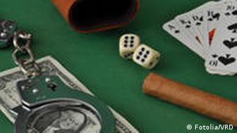 Handcuffs lay on top of money, placed next to dice and cards (Fotolia)