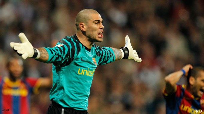 Barcelona's goalkeeper Victor Valdes, reacts while receiving a yellow card during his Spanish La Liga soccer match against Barcelona at the Santiago Bernabeu stadium in Madrid, Saturday, April 16, 2011. (AP Photo/Arturo Rodriguez)