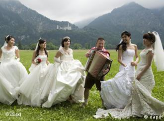 Chinesische Braeute tanzen am Freitag (03.06.11) in Schwangau auf einer Wiese vor dem Schloss Neuschwanstein zusammen mit einem Musikanten. 31 Brautpaare aus China haben am Freitag im Rathaus von Fuessen ihr Eheversprechen erneuert. Anschliessend fuhren sie nach Schwangau, um sich vor dem Schloss Neuschwanstein fotografieren zu lassen. (zu dapd-Text) Foto: Lennart Preiss/dapd