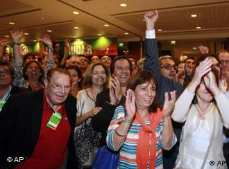 Supporters of the center-right Social Democratic Party, PSD, react to the exit polls results shown on TV screens seconds after voting closed in Portugal Sunday, June 5 2011, at a hotel in Lisbon. Exit polls showed the PSD unseating the ruling Socialist Party. (AP Photo/Armando Franca)