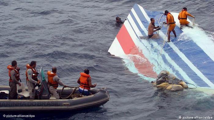 Homens resgatam do mar parte da fuselagem do avião, em que é possível identificar as cores azul e vermelho, da Air France
