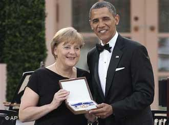 President Barack Obama, right, presents German Chancellor Angela Merkel, left, with the Medal of Freedom during the State Dinner in the Rose Garden of the White House in Washington, Tuesday, June 7, 2011. (AP Photo/Pablo Martinez Monsivais)