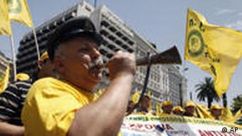 A man blows a horn during a strike in Athens
