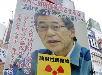 An anti-nuclear demonstrator holds a portrait of outgoingTokyo Electric Power Co.