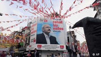 Pedestrians walk by a poster with the image of Kemal Kilicdaroglu, leader of the main opposition Republican People's Party, CHP, in Istanbul, Saturday, June 11, 2011. Around 52 million Turks will vote in the June 12 general elections. The banner reads ''Turkey will breathe a sigh of relief.'' (Foto:Thanassis Stavrakis/AP/dapd)