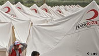 Turkish Red Crescent worker are seen in an almost completed new refugee tent camp in Boynuyogun, Turkey, near the Syrian border, Saturday, June 11, 2011. In the Turkish border town of Yayladagi, authorities set up four field hospitals, each with a 10-bed capacity, for emergency cases. Most of the nearly 50 Syrians, who were wounded in clashes in Jisr al-Shugour or elsewhere recently, are being treated at the state hospital in the Turkish city of Hatay.(Foto:Vadim Ghirda/AP/dapd)