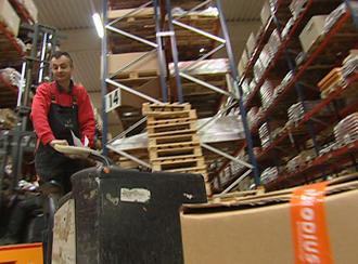 Peter Stitz ist in der Fabrik und transportiert ein großes Paket auf einem Wagen