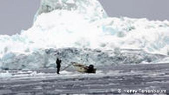 A hunter looks for seals with binoculars