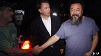 Activist artist Ai Weiwei, right, shakes hand with unidentified foreign journalists gathered outside his home in Beijing, China, Wednesday, June 22, 2011. Chinese state media said Ai Weiwei has been released on bail after confessing to tax evasion, following three month in detention. Ai thanked reporters waiting outside his studio for their support but said under the conditions of his release he was not able to say more.(Foto:Ng Han Guan/AP/dapd)