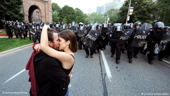 A man and a woman kiss as riot police advance during a protest against the G-20 and the G-8 summits in Toronto, Ontario, Canada on 26 June 2010. The summits, which bring together world leaders and foreign ministers, are being held in the region through the weekend. EPA/JUSTIN LANE