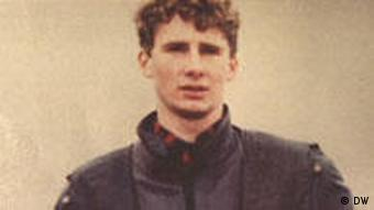 A 20-year-old man looks at the camera in a dated color photograph.
