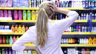 Eine Frau steht in einem Laden vor Kosmetika und überlegt