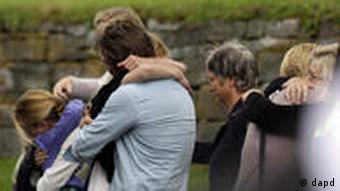 People mourn after a memorial service in Norderhov, Norway, Sunday, July 24, 2011. A Norwegian dressed as a police officer gunned down at least 84 people at an island youth retreat on Friday before being arrested. Investigators are still searching the surrounding waters, where people fled the attack. The same man is believed responsible for an explosion in nearby Oslo that killed seven. (Foto:Frank Augstein/AP/dapd)