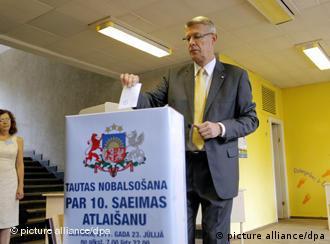 Der Ex-Präsident Lettlands wirft Wahlzettel in eine Urne (Foto: picture-alliance/dpa)