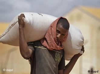 A man carries a bag of food at a food distribution point near the border town of Dadaab, Kenya, Saturday, July 23, 2011. People who can barely stay on their feet due to hunger walk for days or even weeks through parched wasteland to find a meal and water. Many of them also set out to seek help for their ailing children. The drought in the Horn of Africa and the famine in Somalia has left more than two million children at risk of starvation. (Foto:Schalk van Zuydam/AP/dapd)