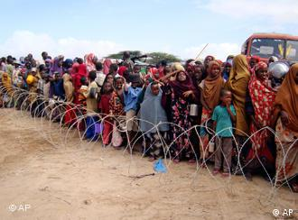 Somalis stand behind barbed wire to receive aid