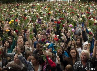 People gather outside Oslo City Hall to participate in a rose march in memory of the victims of Friday's bomb attack and shooting massacre, Norway, Monday, July 25, 2011. Anders Behring Breivik has admitted bombing Norway's capital and opening fire on a political youth group retreat, but he entered a plea of not guilty, saying he wanted to save Europe from Muslim immigration. Police announced Monday that they had dramatically overcounted the number of people slain in a shooting spree at a political youth group's island retreat and were lowering the confirmed death toll from 86 to 68. (Foto:Emilio Morenatti/AP/dapd)