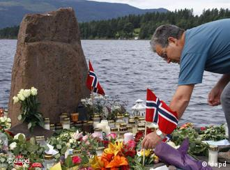 A man places a Norwegian flag between flowers in Utvika in front of the Utoya island, near Oslo, Norway, Tuesday, July 26, 2011, where a gunman Anders Behring Breivik killed at least 76 people. The defense lawyer for Anders Behring Breivik said Tuesday his client's case suggests he is insane, adding that someone has to take the job of defending him but that he will not take instructions from his client. Geir Lippestad told reporters that the suspect in the bombing on the capital and the brutal attack on a youth camp that killed at least 76 people is not aware of the death toll or of the public's response to the massacre that has rocked the country. (Foto:Ferdinand Ostrop/AP/dapd)