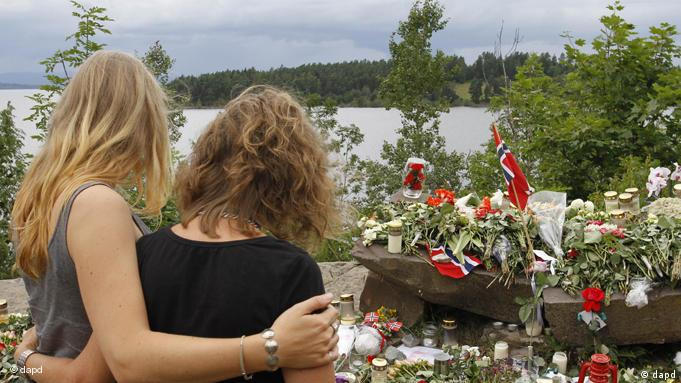 Two young women stand in silence after placing flower near Sundvollen close to the Utoya island, near Oslo, Norway, Tuesday, July 26, 2011, where a gunman Anders Behring Breivik killed at least 68 people. The defense lawyer for the man who confessed to the mass killings of government workers and Labor Party youth in Norway told The Associated Press on Tuesday that there's no way his client will walk free, saying Anders Behring Breivik's rampage was absurd and horrible and he's likely insane. (Foto:Ferdinand Ostrop/AP/dapd)