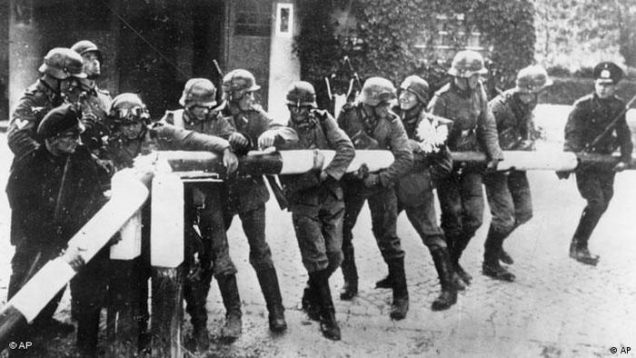 Deutsche Soldaten reißen einen Schlagbaum an der deutsch-polnischen Grenze nieder.