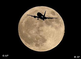 Plane silhouetted against moon