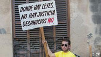 Mann mit Protestplakat vor einem Haus (Foto: DW)