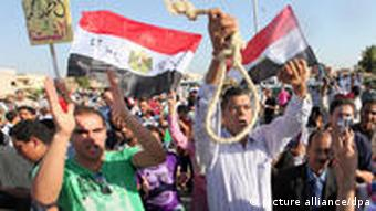 epa02853259 An Egyptian protester (C) holds a hanging rope as others hold the Egyptian National flag outside the police academy, in Cairo, Egypt, 03 August 2011. Supporters of Mubarak and his opponents scuffled on 03 August in the morning outside a makeshift courtroom near Cairo ahead of the start of his trial on charges of ordering the killing of protesters earlier this year. People gathered outside the Police Academy on the outskirts of Cairo where Mubarak, his two sons, former interior minister Habib al-Adli and six senior policemen appearing at the opening of the trial, amid tight security. EPA/KHALED ELFIQI +++(c) dpa - Bildfunk+++