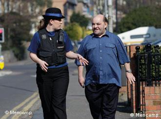 Policewoman walking along street with intellectually disabled man.