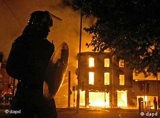 A building burns as a riot police officer watches in Croydon, south London, Monday, Aug. 8, 2011. Violence and looting spread across some of London's most impoverished neighborhoods on Monday, with youths setting fire to shops and vehicles, during a third day of rioting in the city that will host next summer's Olympic Games. (Foto:PA, Dominic Lipinski/AP/dapd) UNITED KINGDOM OUT, NO SALES, NO ARCHIVE