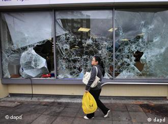 A woman walks past a damaged supermarket in Ealing, west London, after a night of rioting, Tuesday, Aug. 9, 2011. In London, groups of young people rampaged for a third straight night, setting buildings, vehicles and garbage dumps alight, looting stores and pelting police officers with bottles and fireworks into early Tuesday. The spreading disorder was an unwelcome warning of the possibility of violence during London's 2012 Summer Olympics, less than a year away. (Foto:Lefteris Pitarakis/AP/dapd)