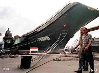 FILE - In this May 27, 1997 file photo, workers walk in front of aircraft carrier Varyag at a dockyard in Mykolayiv, Ukraine. China officially acknowledged Wednesday, July 27, 2011, it is rebuilding the aircraft carrier it bought more than a decade ago, but said the refurbished ship will be used only for research and training. (AP Photo/Efrem Lukatsky, File)