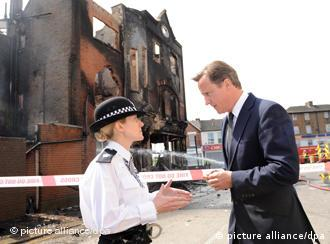 epa02860859 British Prime Minister David Cameron talks to Acting Borough Police Commander Superintendent Jo Oakley in Croydon, south London, England, on 09 August 2011 where he saw damage to shops and residences carried out by rioters on 08 August 2011. Reports state that after a third day of violence in which police have clashed with rioters in Croydon and vehicles have been set on fire in Peckham and Lewisham. This follows two nights of violence over the weekend after the police shooting of a man in Tottenham. More than 200 people have been arrested and 35 police officers injured. Violence erupted in reaction to a fatal shooting incident in Tottenham, in which a policeman was injured on 04 August and a local 29-year-old man named as Mark Duggan killed by armed officers. EPA/STEFAN ROUSSEAU UK AND IRELAND OUT; NO COMERCIAL USE