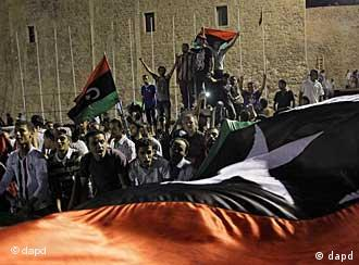 Libyans hold a huge flag as they celebrate overrunning the main Muammar Gadhafi compound Bab Al-Aziziya in Tripoli, Libya, early Wednesday, Aug. 24, 2011. Hundreds of Libyan rebels stormed the compound Tuesday, charging wildly through the symbolic heart of the crumbling regime as they killed loyalist troops, looted armories and knocked the head off a statue of the besieged dictator. (Foto:Sergey Ponomarev/AP/dapd)